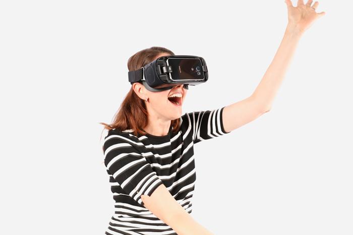 A woman uses a smartphone-based virtual reality headset.